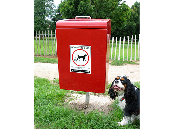 red dog bin with dog bin sticker on with dog sitting by the side of it