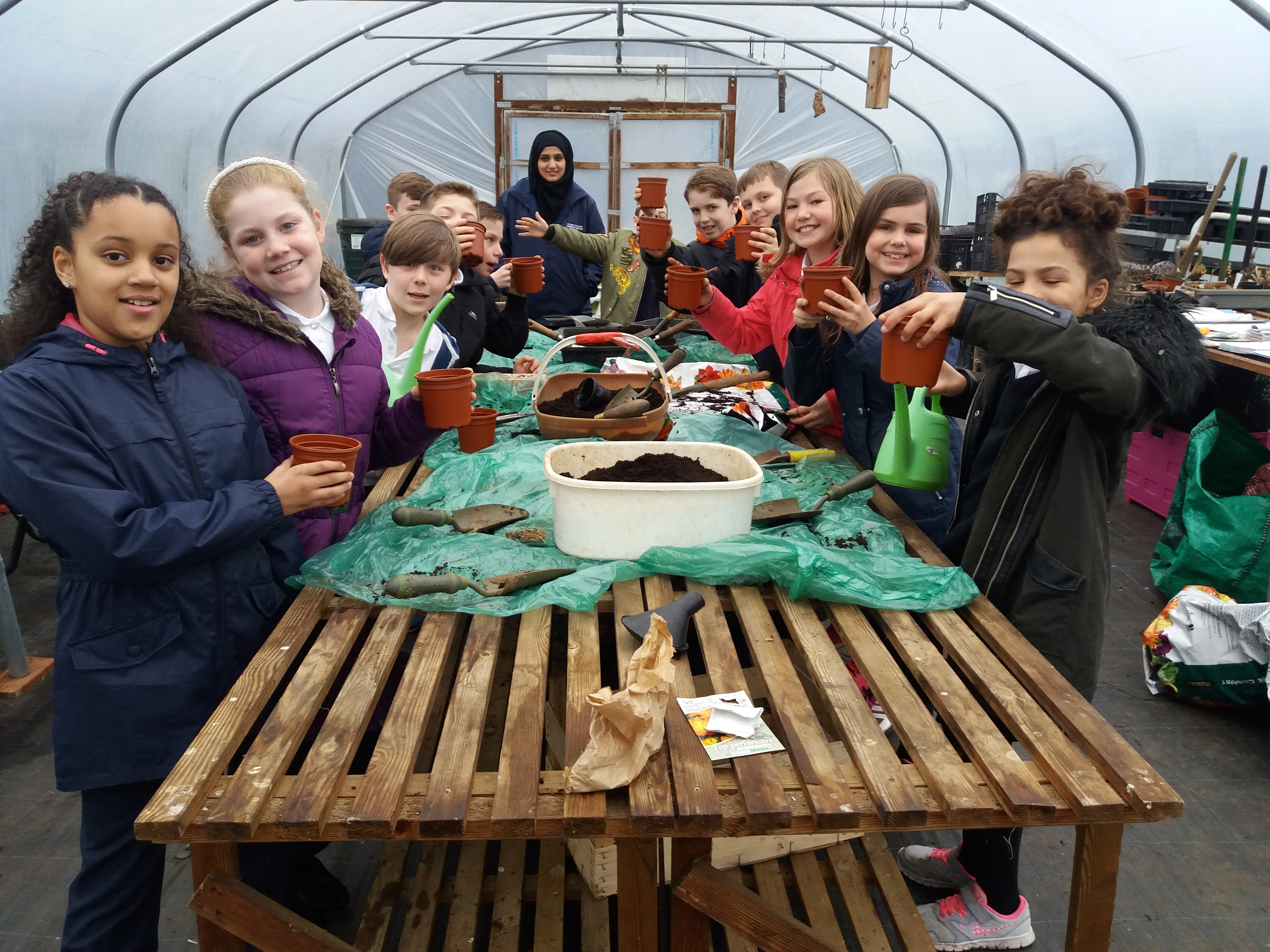 Photo of children at St Mary and St Giles School having a gardening session in the school polytunnel.