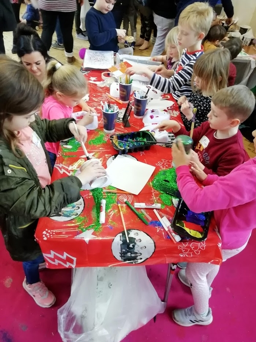 children at an indoor play scheme gathered around a table doing arts and crafts