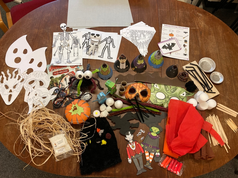 Selection of Halloween children's paper crafts laid out on a table including masks, puppets and models