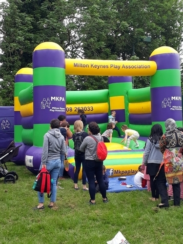 image showing a play scheme at a recreation ground with children on a bouncy castle and parents watching
